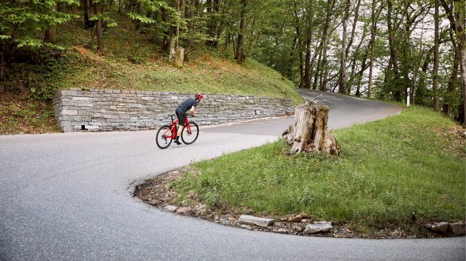 bmc alpenchallenge amp sport one flat bar electric road bike being ridden up a hill